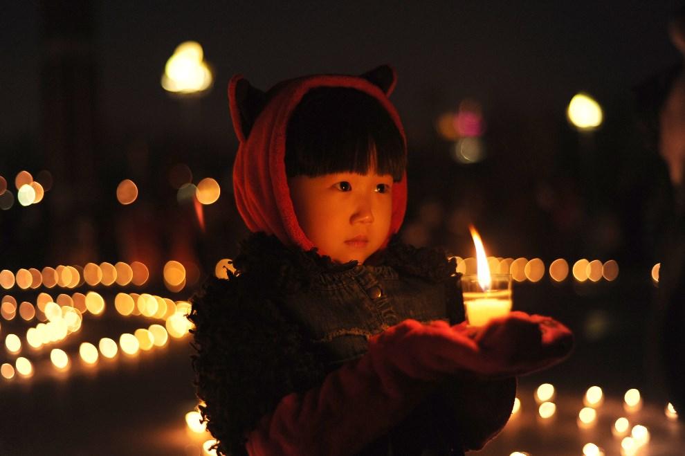 1.CHINY, Daqing, 21 kwietnia 2013: Dziewczynka ze świecą podczas modlitwy w intencji ofiar trzęsienia ziemi.  AFP PHOTO