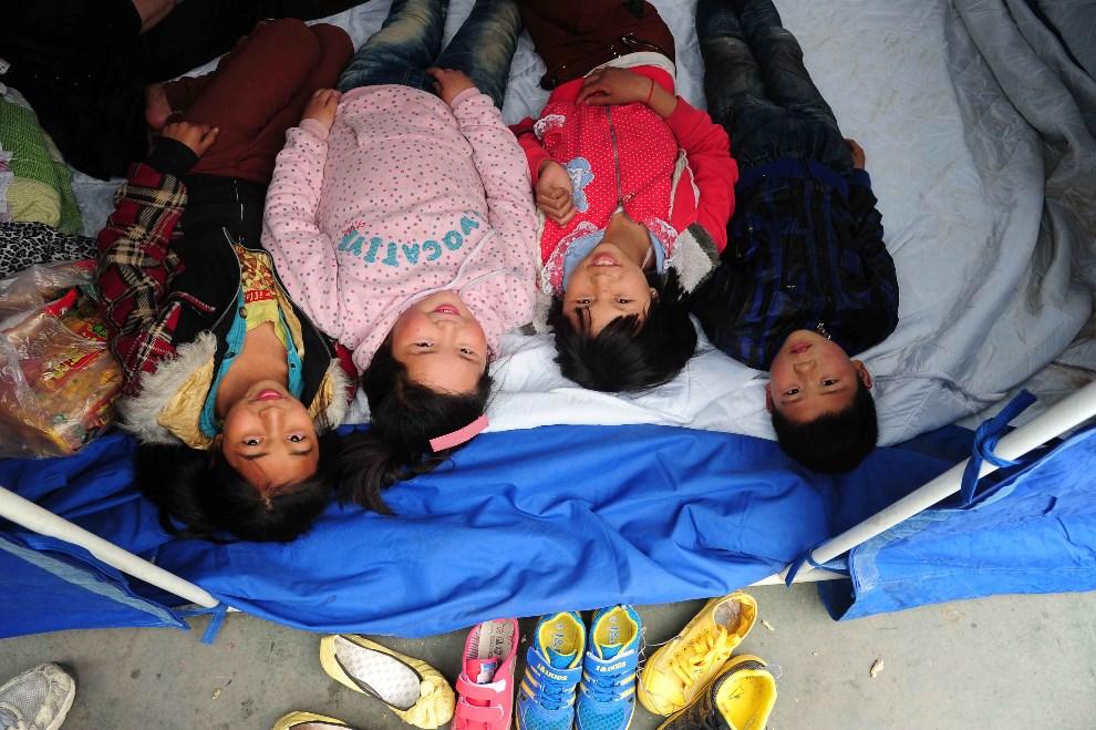 20.CHINY, Ya'an, 21 kwietnia 2013: Dzieci leżące u wejścia do namiotu. AFP PHOTO