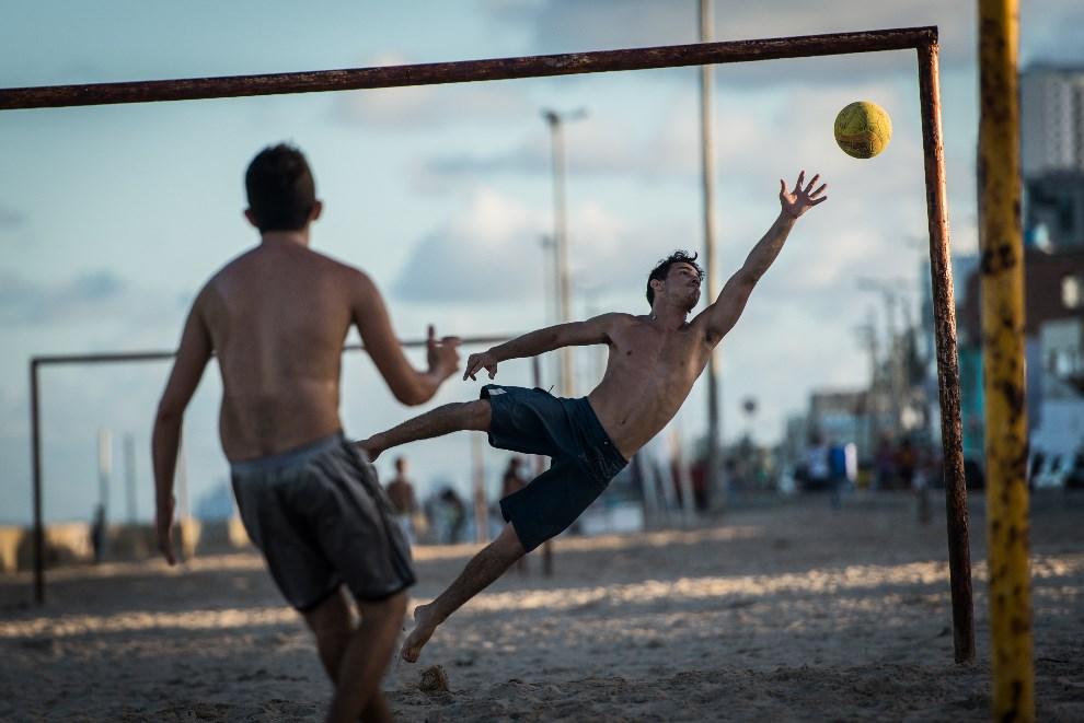 20.BRAZYLIA, Recife, 14 kwietnia 2013: Chłopcy grający w piłkę na plaży. AFP PHOTO/Yasuyoshi CHIBA