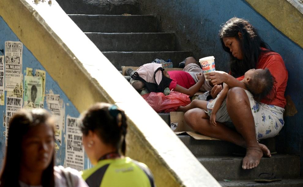 22.FILIPINY, Manila, 18 grudnia 2012: Bezdomna matka z dwójką dzieci. AFP PHOTO/NOEL CELIS