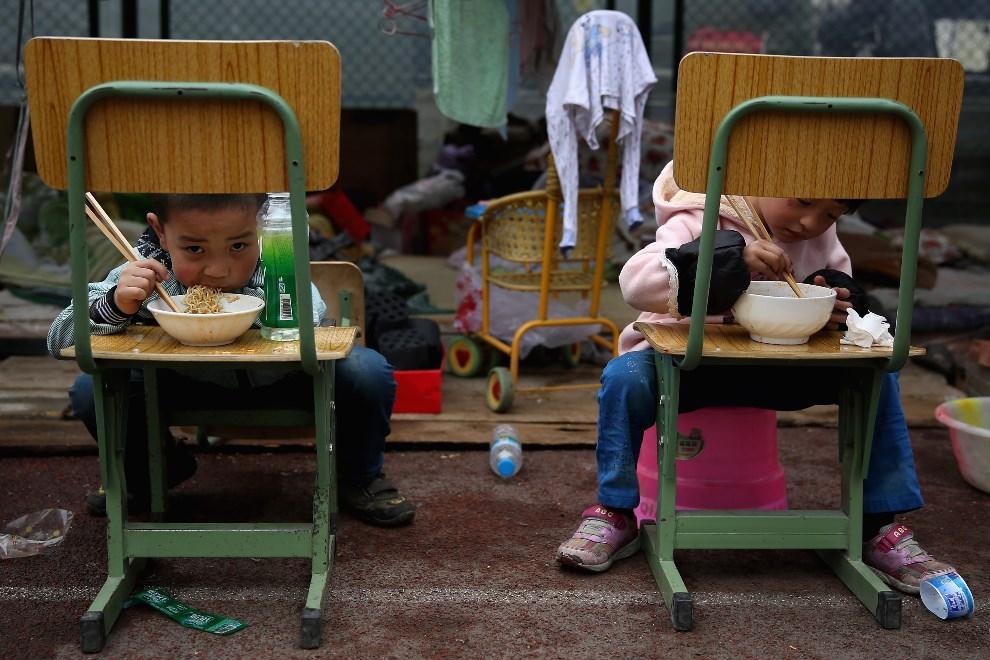 23.CHINY, Chengdu, 22 kwietnia 2013: Dzieci z miasteczka namiotowego podczas posiłku. ( Foto: Feng Li/Getty Images)