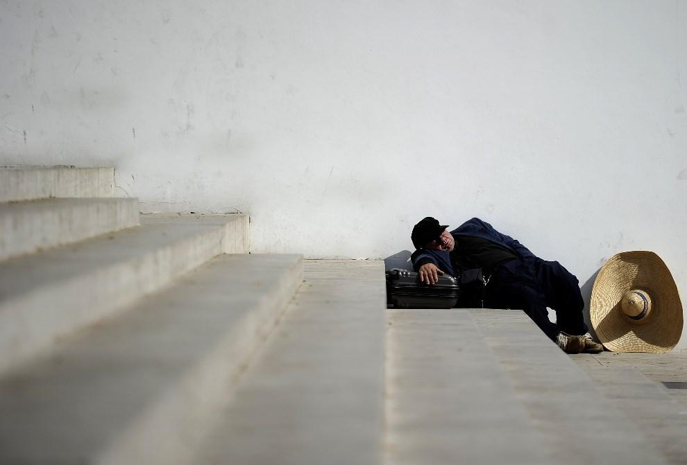 25.WŁOCHY, Rzym, 4 kwietnia 2012: Bezdomny śpiący na schodach Ara Pacis. AFP PHOTO/ FILIPPO MONTEFORTE