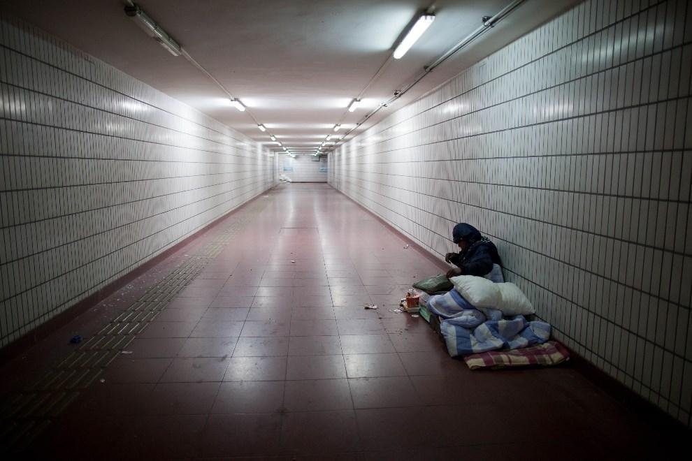 26.CHINY, Pekin, 7 grudnia 2012: Bezdomny nocujący w podziemnym przejściu. AFP PHOTO / Ed Jones