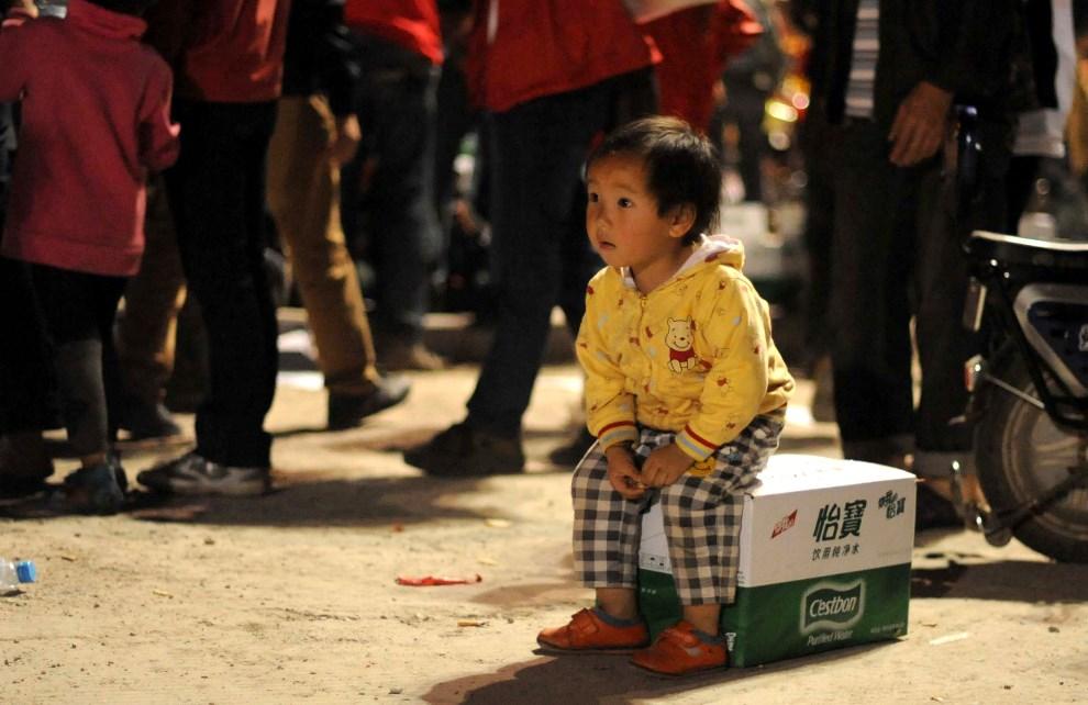 28.CHINY, Ya'an, 21 kwietnia 2013: Dziewczynka na kartonie z butelkami z wodą.  AFP PHOTO