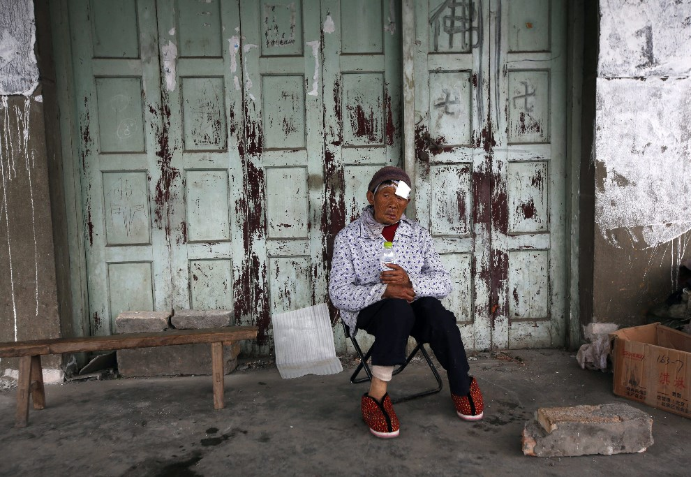 29.CHINY, Ya'an, 21 kwietnia 2013: Ranna Chen Biying siedzi przed wejściem do swojego domu. EPA/HOW HWEE YOUNG Dostawca: PAP/EPA.