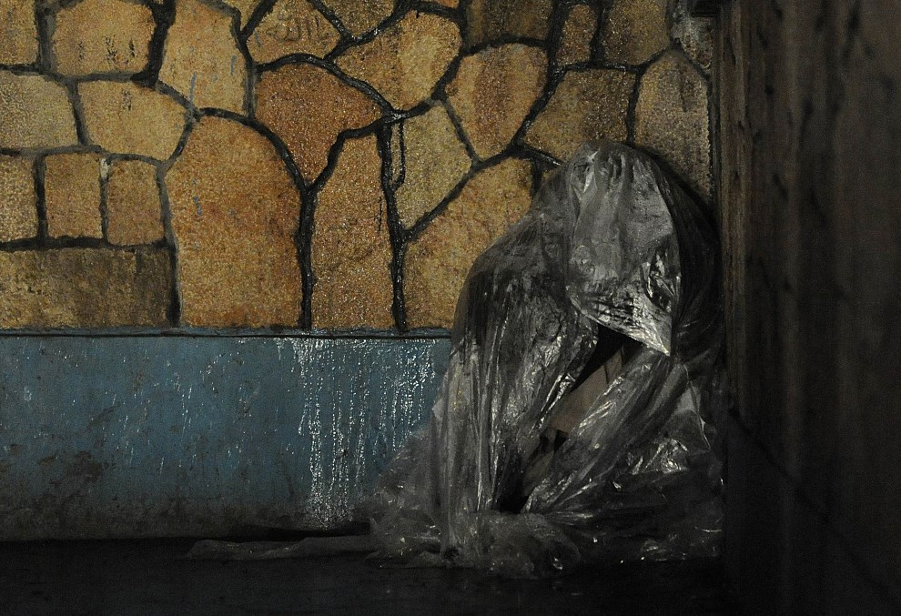 2.AFGANISTAN, Mazar-i Szarif, 9 lutego 2012: Bezdomny mężczyzna chroni się przed deszczem. AFP PHOTO/ Qais Usyan