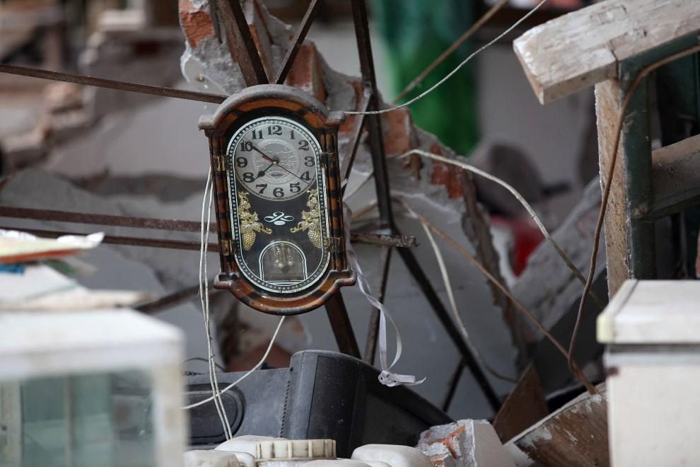 34.CHINY , Ya'an, 20 kwietnia 2013: Zegar wiszący na gruzach jednego ze zniszocznych domów.  AFP PHOTO