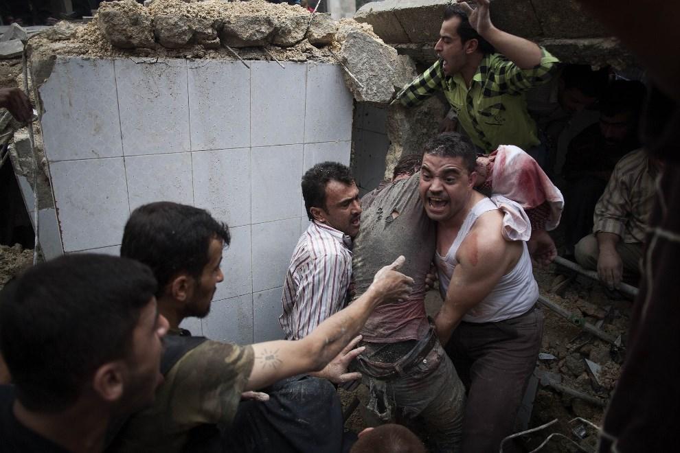 5.SYRIA, Aleppo: Mężczyźni ratują ludzi uwięzionych w ruinach ostrzelanego meczetu. AFP PHOTO/FABIO BUCCIARELLI