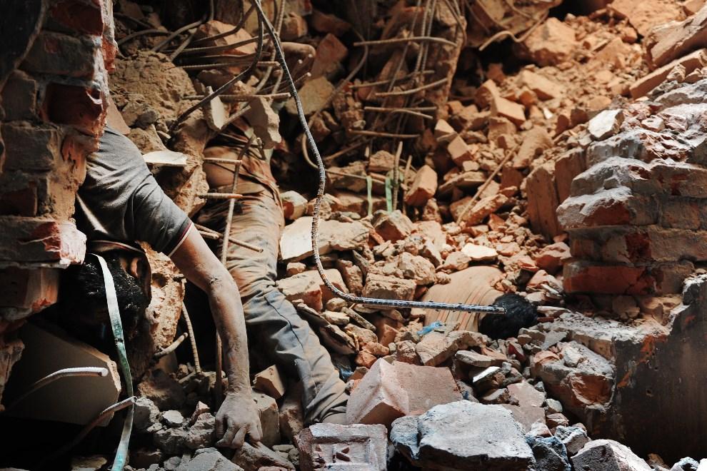 6.BANGLADESZ, Savar, 25 kwietnia 2013: Ofiary pogrzebane w gruzach zawalonego budynku. AFP PHOTO/Munir uz ZAMAN