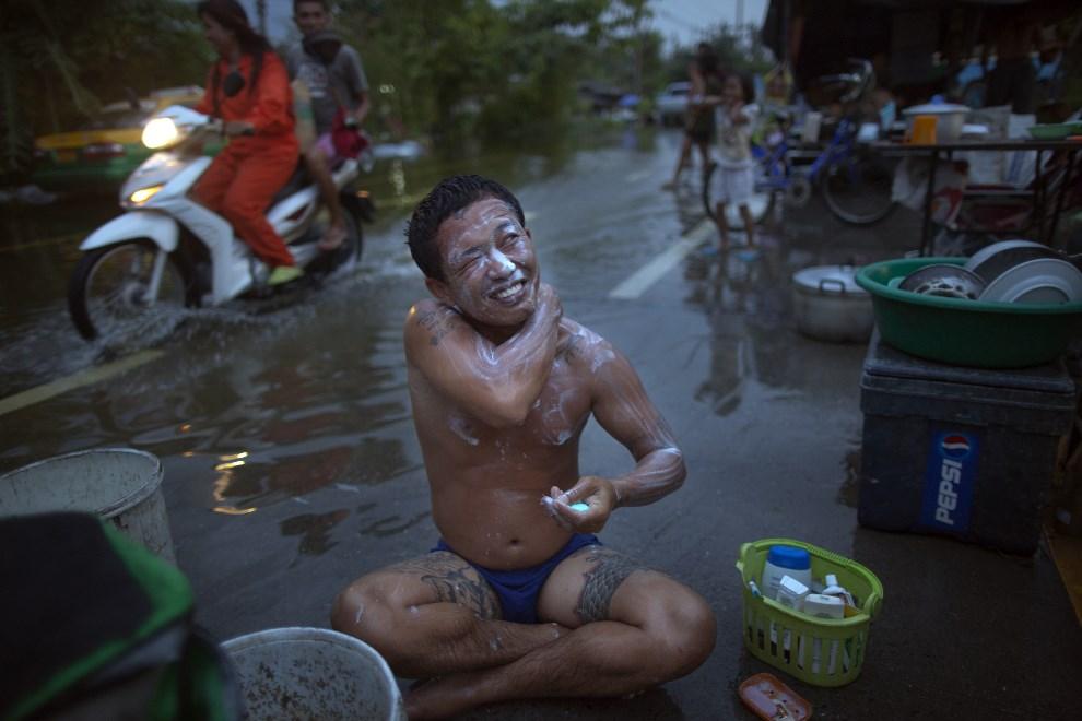 6.TAJLANDIA, Pathum Thani, 21 października 2011: Bezdomny mężczyzna podczas kąpieli na ulicy. (Foto: Paula Bronstein/Getty Images)