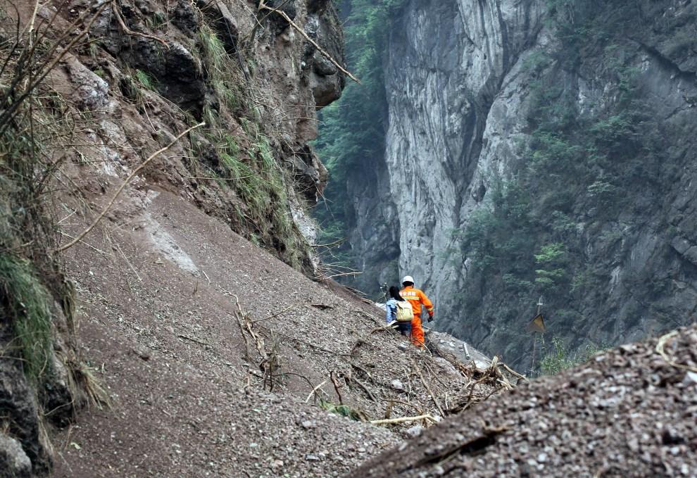 9.CHINY, Ya'an, 21 kwietnia 2013: Odnaleziona kobieta schodzi po obsuniętym zboczu w towarzystwie ratownika.  AFP PHOTO
