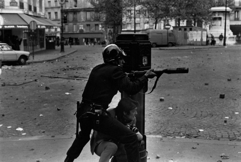 23. FRANCJA, Paryż, maj 1968: Fotoreporter i policjant na ogarniętej walkami ulicy. (Foto: Reg Lancaster/Getty Images)