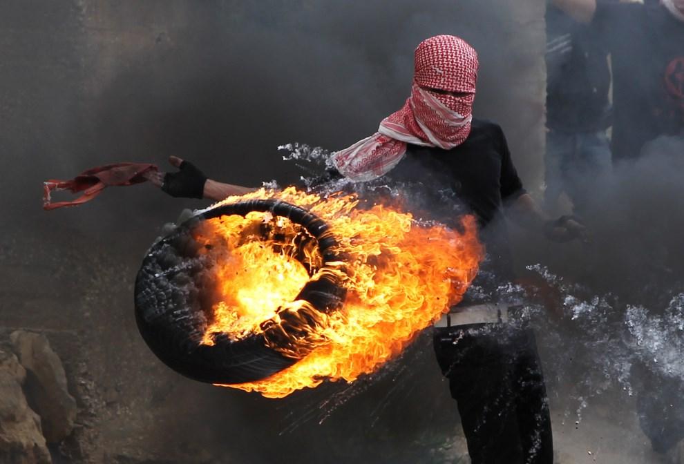 9.ZACHODNI BRZEG, Bajtunija, 15 maja 2013: Palestyńczyk podpala oponę w trakcie walk z izraelskimi żołnierzami.  AFP PHOTO/ ABBAS MOMANI