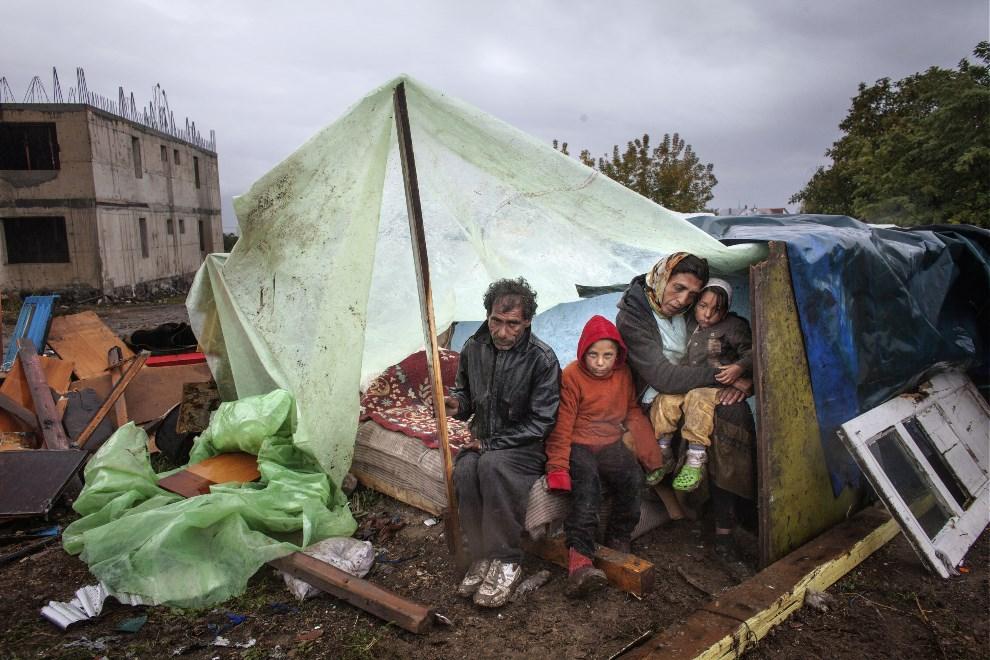 11.RUMURNIA, Eforie Sud, 30 września 2013: Romska rodzina czeka na nakaz opuszczenia prowizorycznego obozowiska.  AFP PHOTO / MUGUR VARZARIU