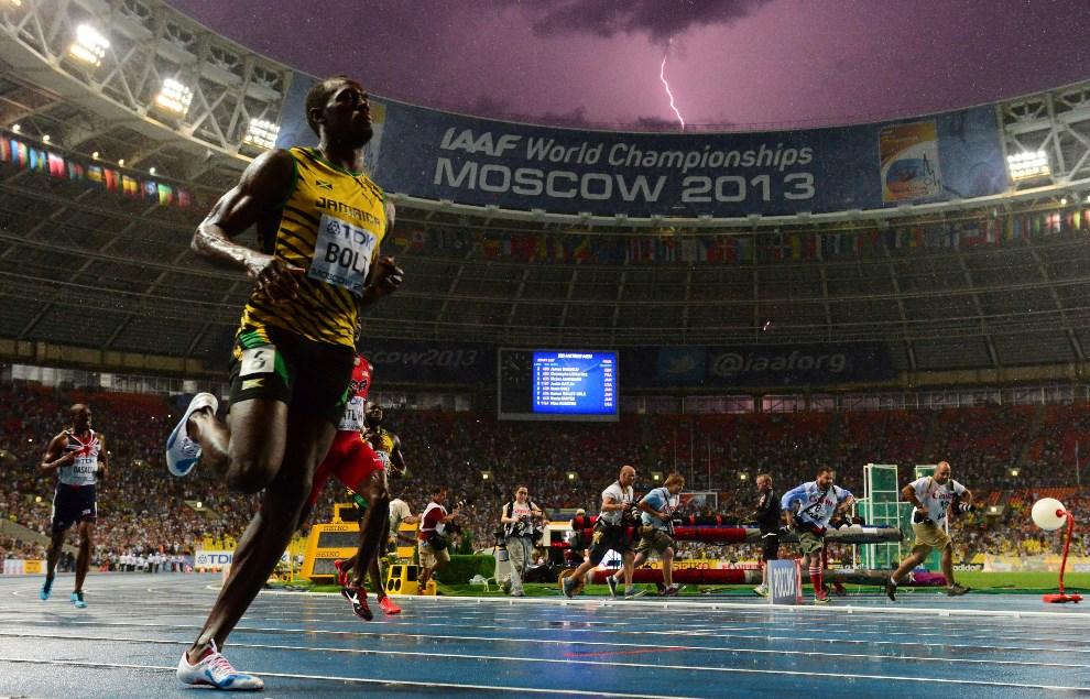 12.ROSJA, Moskwa, 11 sierpnia 2013: Jamajczyk Usain Bolt wygrywa bieg finałowy na dystansie 100 metrów (w tle piorun – ang. bolt – uderzający w pobliży stadionu na Łużnikach). AFP FOTO:  / OLIVIER MORIN