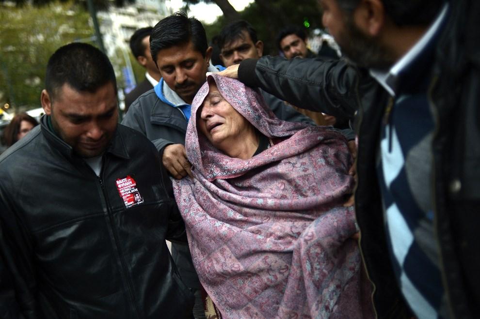 14.GRECJA, Ateny, 18 grudnia 2013: Matka zabitego przez neonazistów, 27-letniego Pakistańczyka, opuszcza salę sądową. AFP PHOTO / ARIS MESSINIS