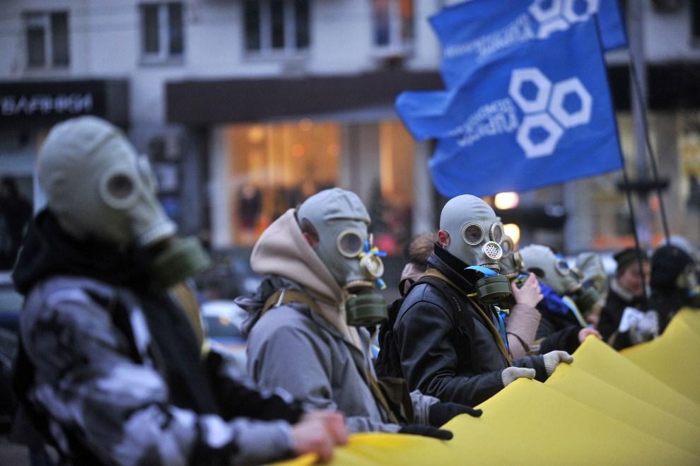 14.UKRAINA, Kijów, 13 grudnia 2013: Protestujący w maskach przeciwgazowych trzymają flag Ukrainy. AFP PHOTO/ GENYA SAVILOV