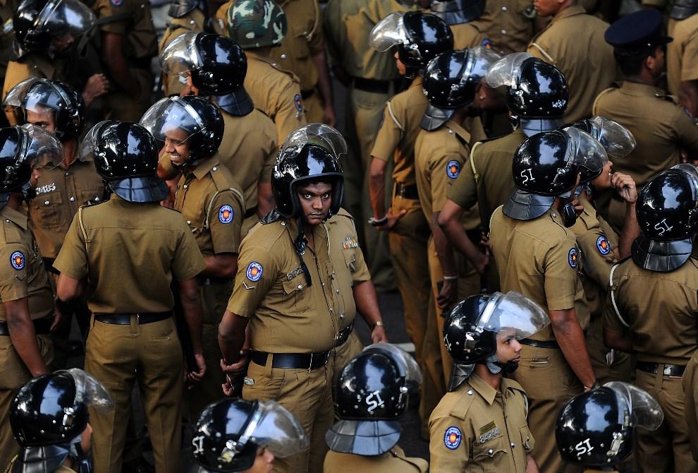 15.SRI LANKA, Colombo, 11 grudnia 2013: Oddział policji blokujący drogę do pałacu prezydenckiego. AFP PHOTO/ Ishara S.KODIKARA