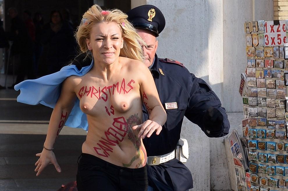 15.WŁOCHY, Rzym, 19 grudnia 2013: Inna Szewczenko, liderka FEMEN'u, ucieka przed policjantem. AFP PHOTO / GABRIEL BOUYS
