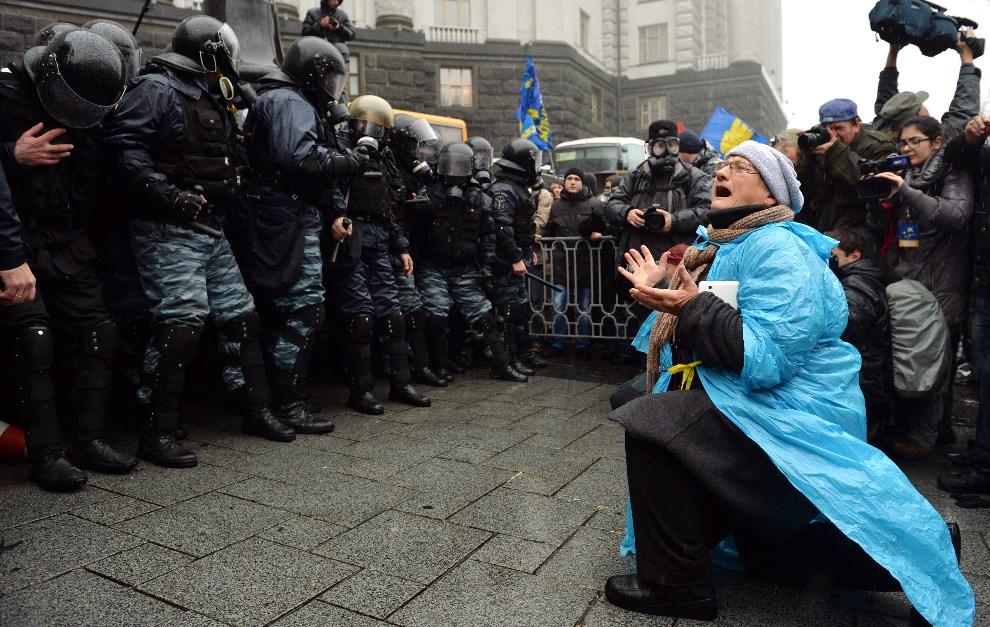 16.UKRAINA, Kijów, 25 listopada 2013: Kobieta klęcząca przed oddziałem milicji. AFP PHOTO/ SERGEI SUPINSKY