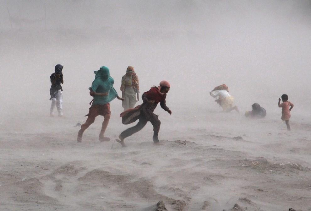 18.PAKISTAN, Lahore, 15 października 2013: Ludzie chroniący się podczas burzy.  AFP PHOTO/ Arif ALI