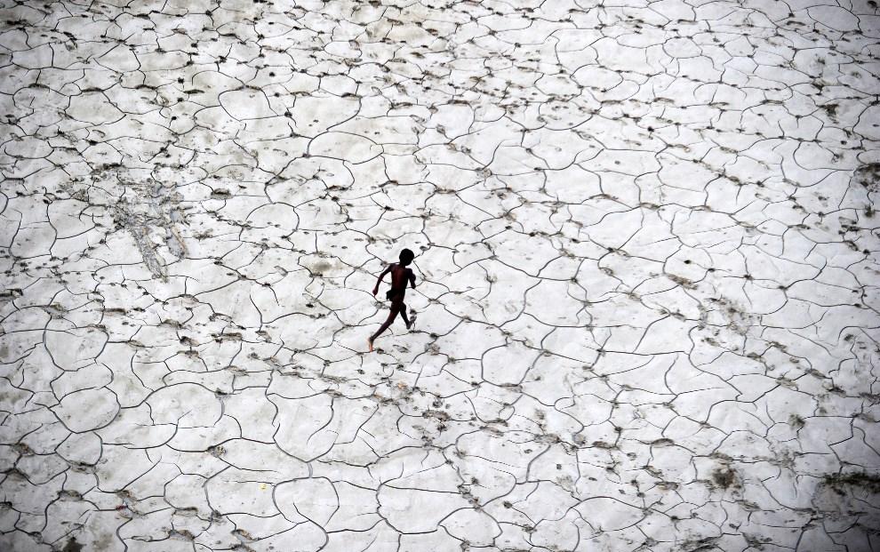 19.INDIE, Allahabad, 25 października 2013: Dziecko bawiące się w wyschniętym korycie rzeki. AFP PHOTO/ SANJAY KANOJIA