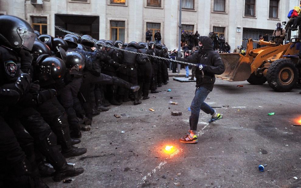19.UKRAINA, Kijów, 1 grudnia 2013: Protestujący atakuje oddział milicji łańcuchem. AFP PHOTO/GENYA SAVILOV