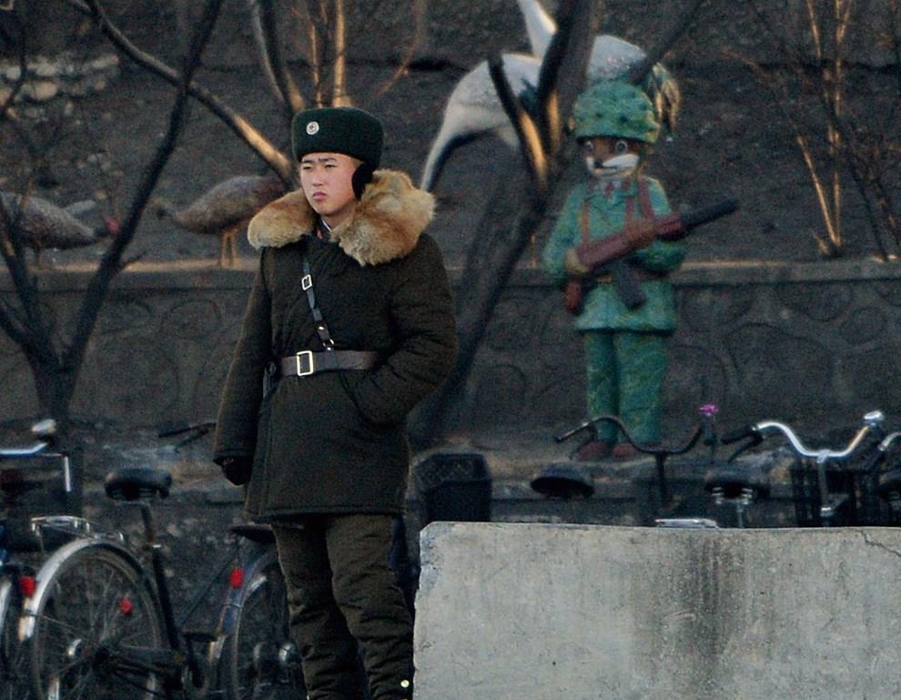 20.CHINY, Dandong, 17 grudnia 2013: Żołnierz północnokoreański nad brzegiem rzeki Yalu (oddzielającej Koreę Północną od Południowej). AFP PHOTO/Mark RALSTON