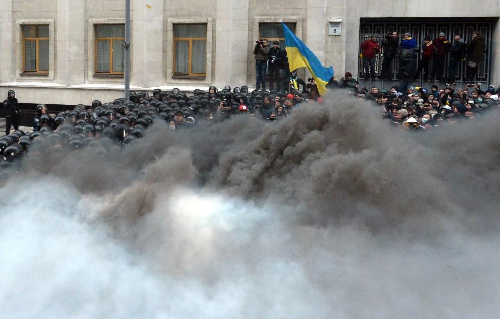 21.UKRAINA, Kijów, 17 grudnia 2013: Oddział milicji osłonięty przez dym z płonących opon. AFP PHOTO/VASILY MAXIMOV