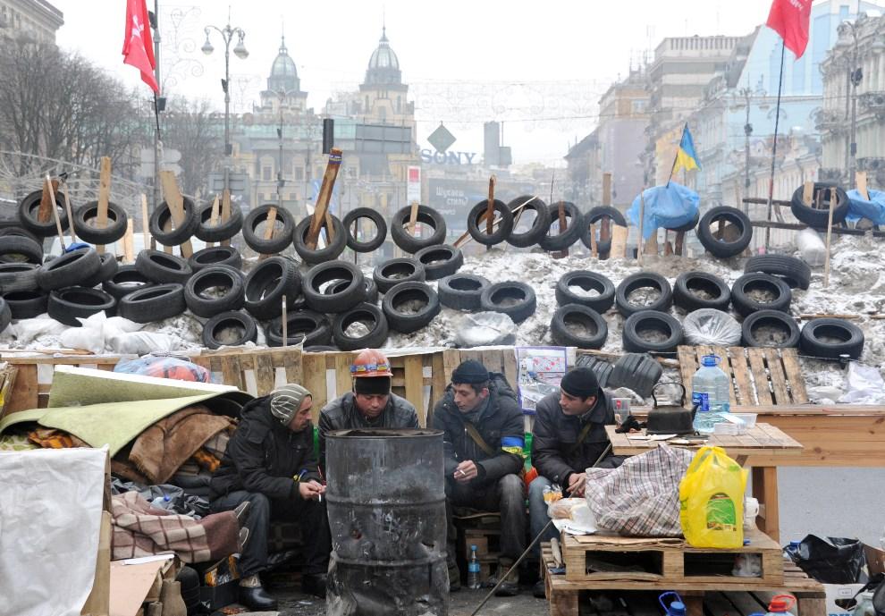 24.UKRAINA, Kijów, 12 grudnia 2013: Protestujący mężczyźni siedzą przed barykadą wniesioną w centrum miasta. AFP PHOTO/ VIKTOR DRACHEV