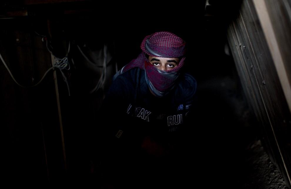 24.STREFA GAZY, Rafah, 9 grudnia 2013: Mężczyzna pracujący w tunelu używanym przez przemytników. AFP PHOTO/MAHMUD HAMS