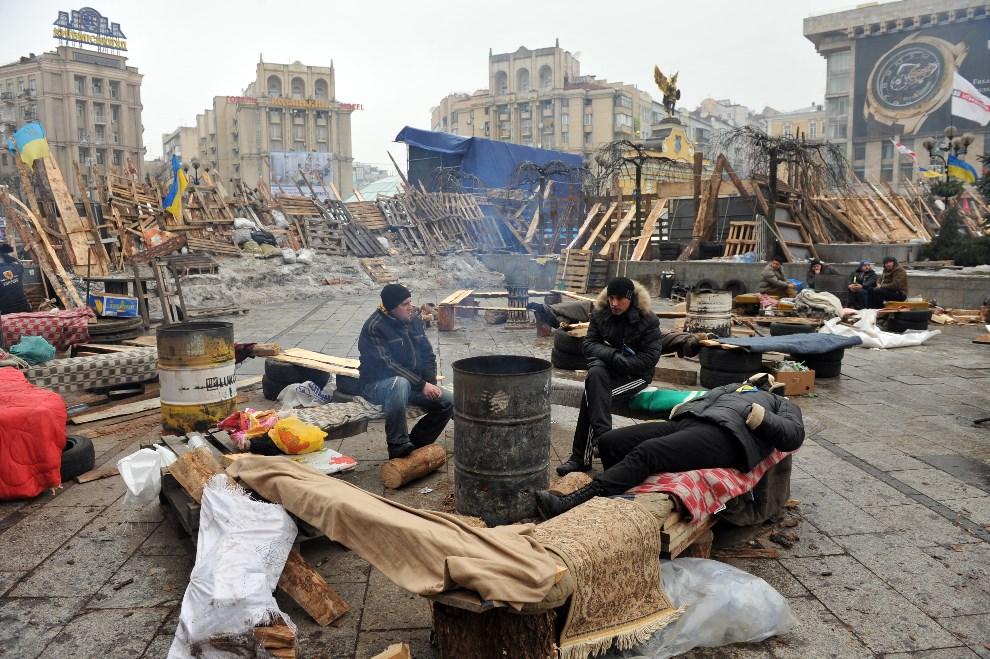 25.UKRAINA, Kijów, 12 grudnia 2013: Mężczyźni pilnujący barykady przy Placu Niepodległości. AFP PHOTO/ YURIY DYACHYSHYN