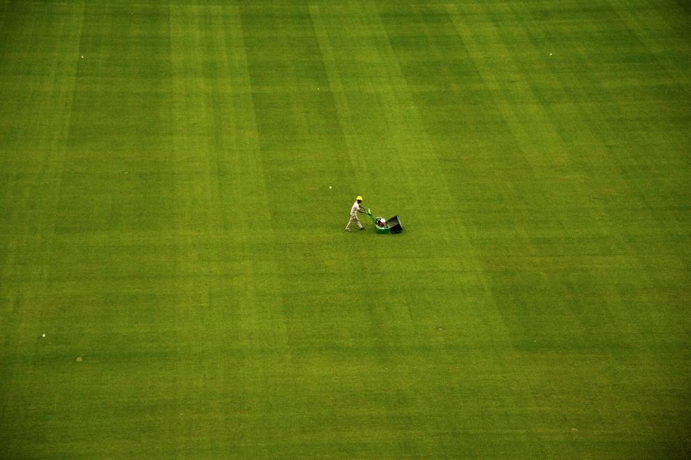 26.BRAZYLIA, Sao Paulo, 16 grudnia 2013: Mężczyzna kosi trawę na stadionie Corinthians Arena. AFP PHOTO / CHRISTOPHE SIMON