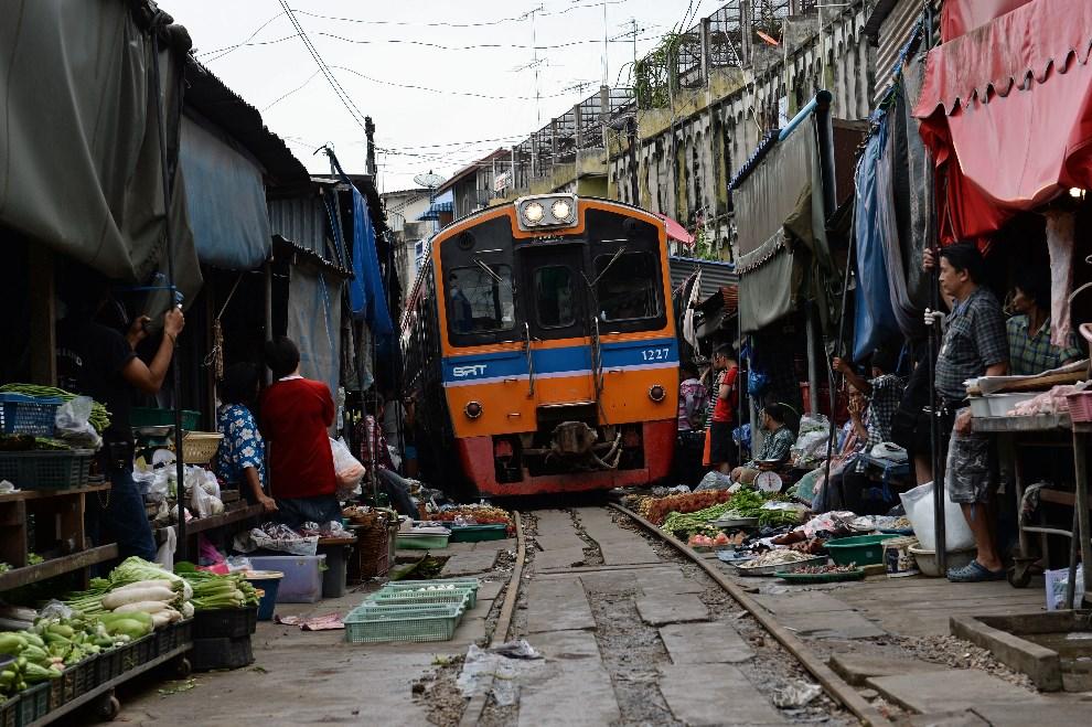 27.TAJLANDIA, Maeklong, 25 czerwca 2013: Pociąg przejeżdża między straganami. AFP FOTO: /Christophe ARCHAMBAULT
