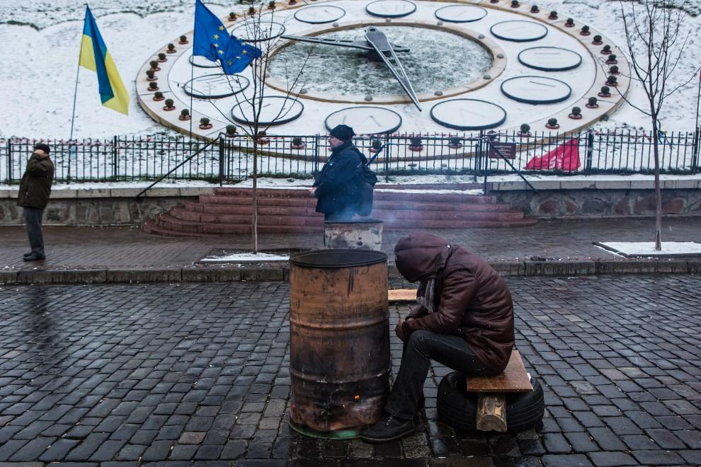 28.UKRAINA, Kijów, 7 grudnia 2013: Mężczyzna drzemiący przy koksowniku. (Foto:  Brendan Hoffman/Getty Images)