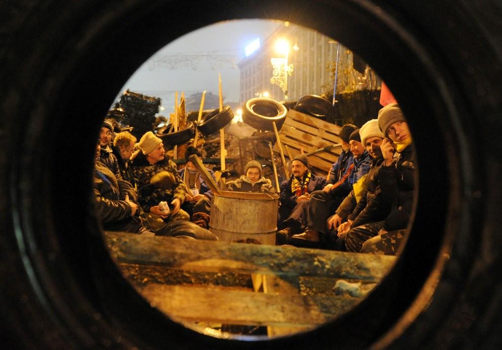 29.UKRAINA, Kijów, 12 grudnia 2013: Mężczyźni na barykadzie przy Placu Niepodległości.  AFP PHOTO/ VIKTOR DRACHEV