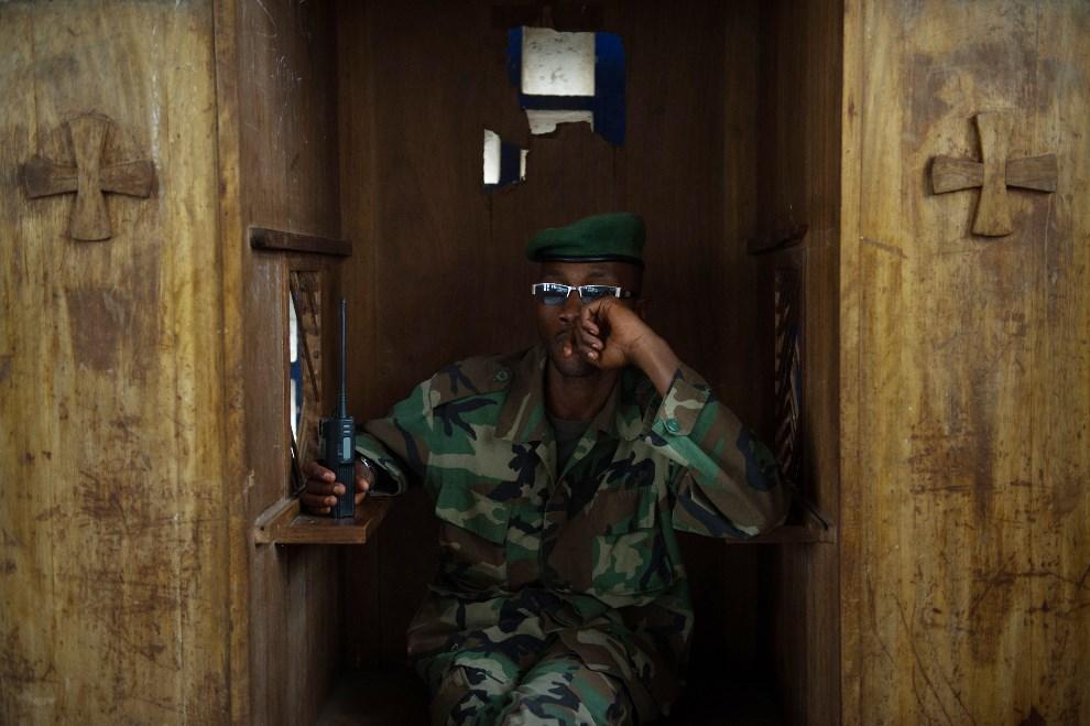 31.DEMOKRATYCZNA REPUBLIKA KONGA, Rumangabo, 20 lipca 2013: Żołnierz ugrupowania M23 siedzi w konfesjonale podczas szkolenia dla rebeliantów. AFP FOTO: /PHIL MOORE