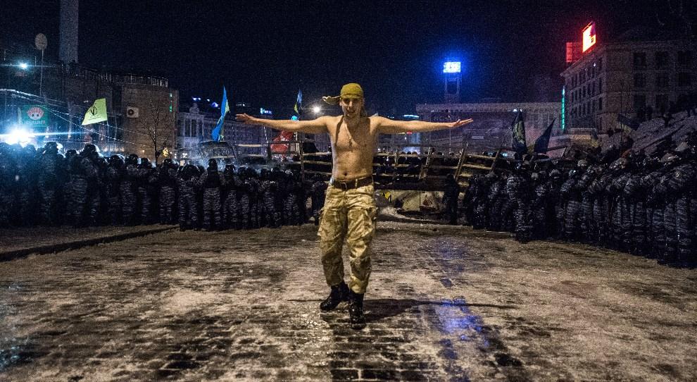 32.UKRAINA, Kijów, 11 grudnia 2013: Protestujący mężczyzna na tle oddziału milicji. AFP PHOTO/ DMITRY SEREBRYAKOV
