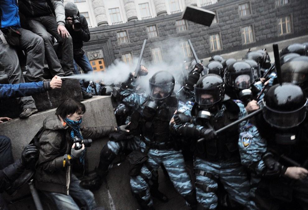 36.UKRAINA, Kijów, 24 listopada 2013: Protestujący rozpylają gaz łzawiący w kierunku milicjantów. AFP PHOTO / GENYA SAVILOV