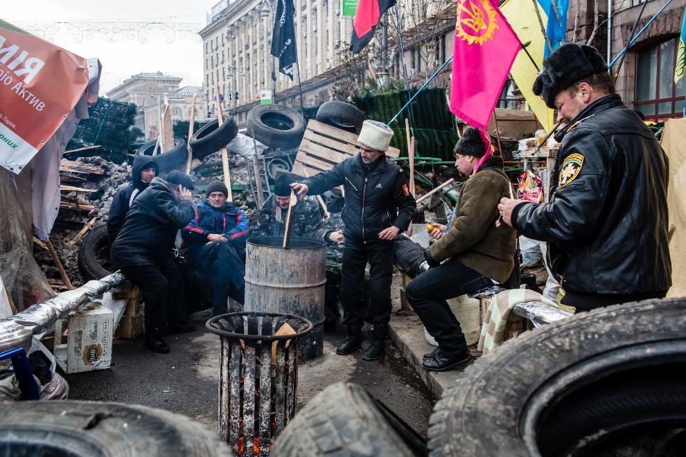 38.UKRAINA, Kijów, 13 grudnia 2013: Protestujący grzeją się przy ogniu. (Foto:  Brendan Hoffman/Getty Images)