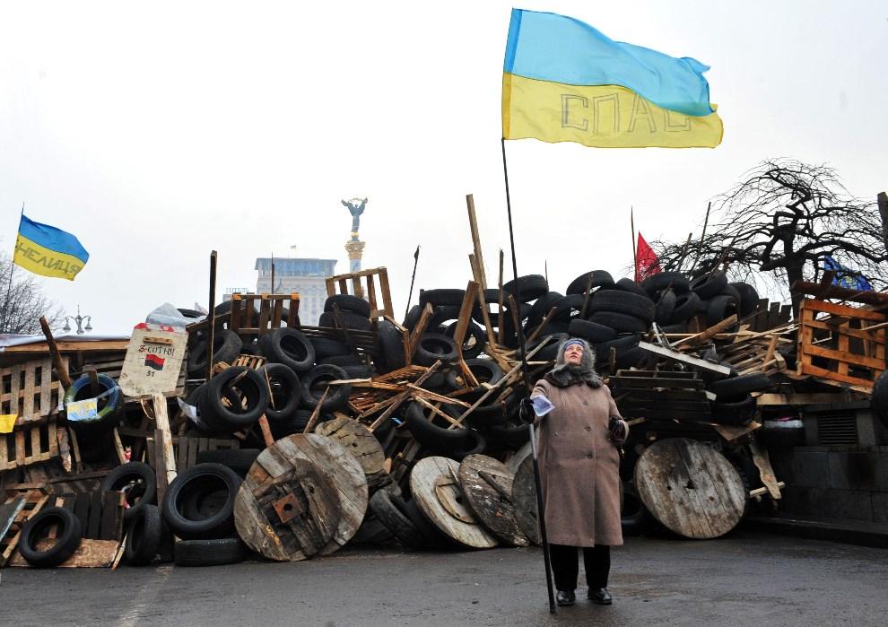 39.UKRAINA, Kijów, 17 grudnia 2013: Kobieta z flagą przed barykadą. AFP PHOTO / YURIY DYACHYSHYN