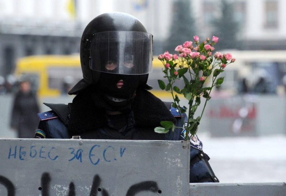 40.UKRAINA, Kijów, 17 grudnia 2013: Milicjant z kwiatami zatkniętymi za tarczą. AFP PHOTO/ VIKTOR DRACHEV