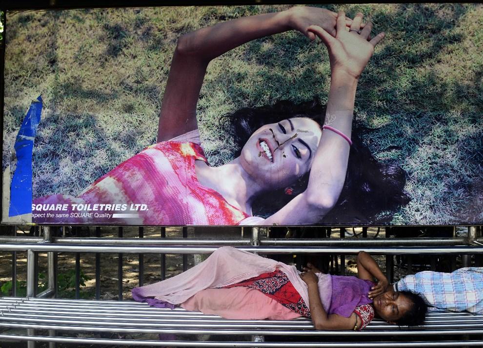4.BANGLADESZ, Dhaka, 18 września 2013: Bezdomna kobieta śpiąca pod billboardem reklamowym. AFP PHOTO/ Munir uz ZAMAN