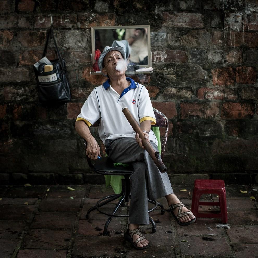 4.WIETNAM, Hanoi, 20 lica 2013: Uliczny fryzjer palący fajkę. (Foto: Chris McGrath/Getty Images)