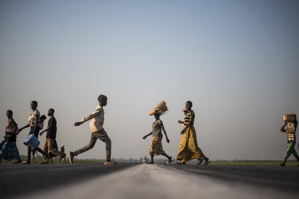 5.REPUBLIKA ŚRODKOWOAFRYKAŃSKA, Bangui, 14 grudnia 2013: Grupa ludzi zmierzająca w kierunku obozu dla uchodźców. AFP PHOTO / FRED DUFOUR