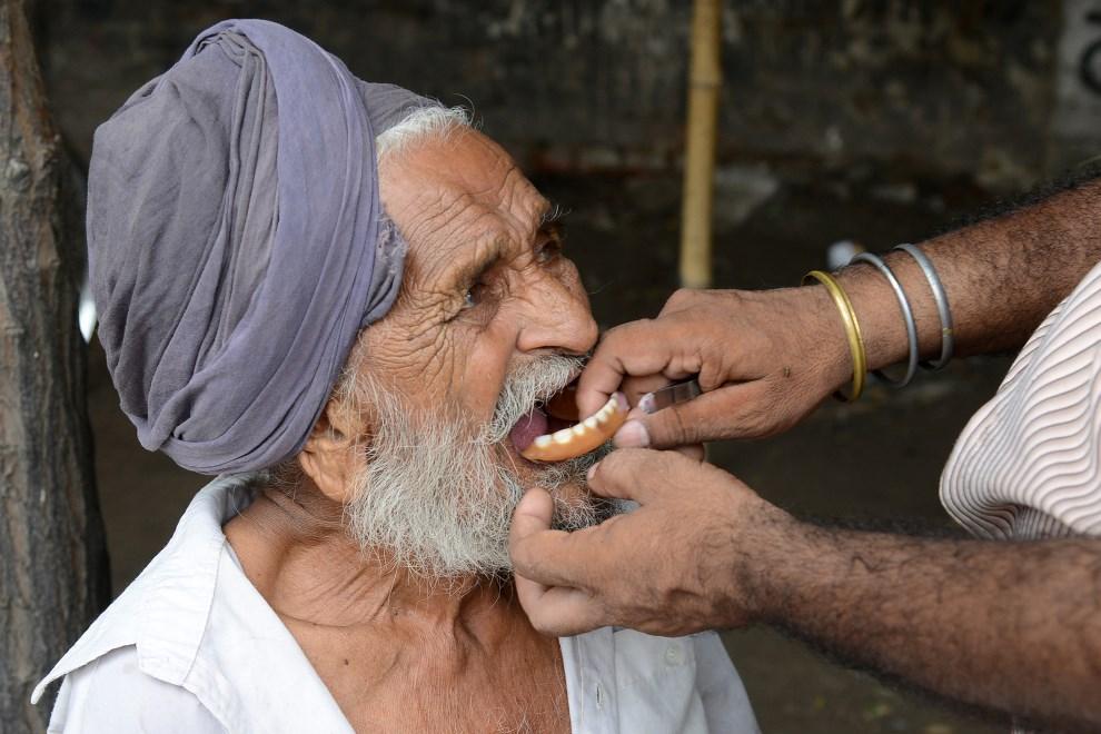 7.INDIE, Amritsar, 16 lipca 2013: Uliczny stomatolog dopasowuje protezę swojemu pacjentowi. AFP FOTO:  /NARINDER NANU