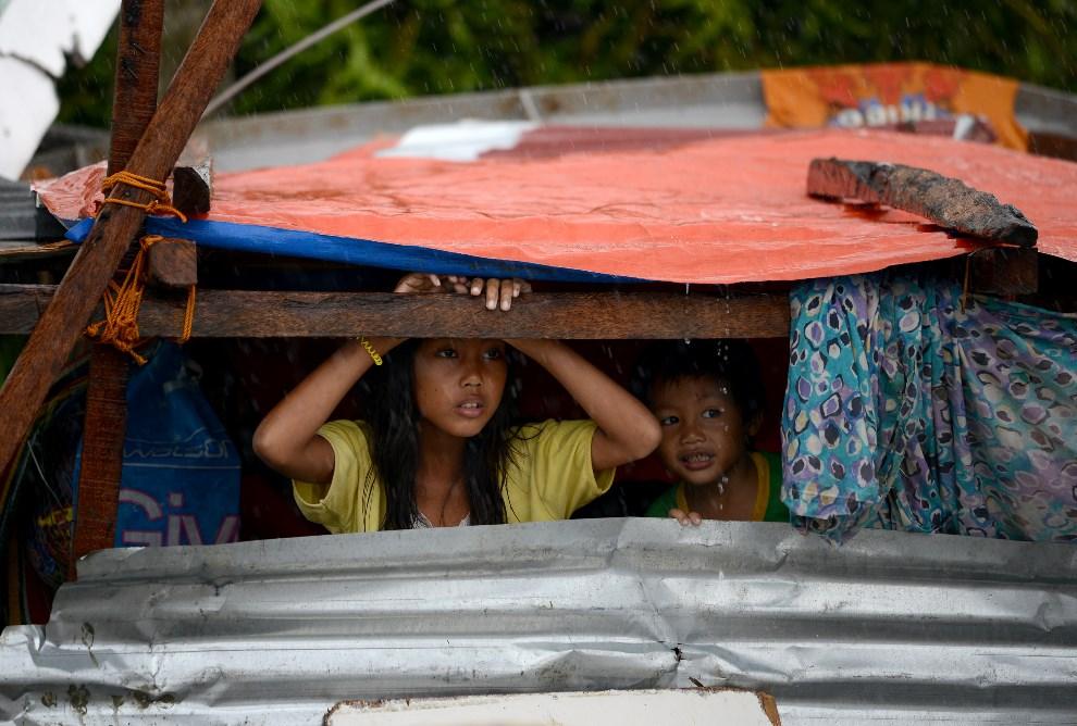 8.FILIPINY, Tacloban, 10 listopada 2013: Dzieci chroniące się w prowizorycznym szałasie. AFP PHOTO/NOEL CELIS