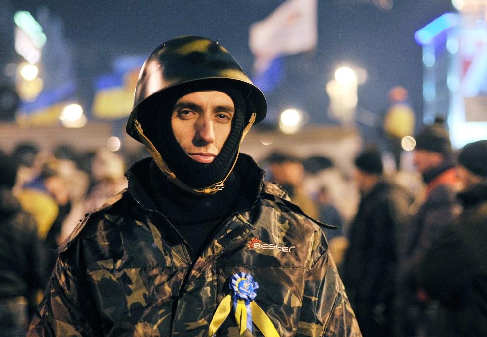 9.UKRAINA, Kijów, 14 grudnia 2013: Mężczyzna pilnujący barykady. AFP PHOTO / GENYA SAVILOV