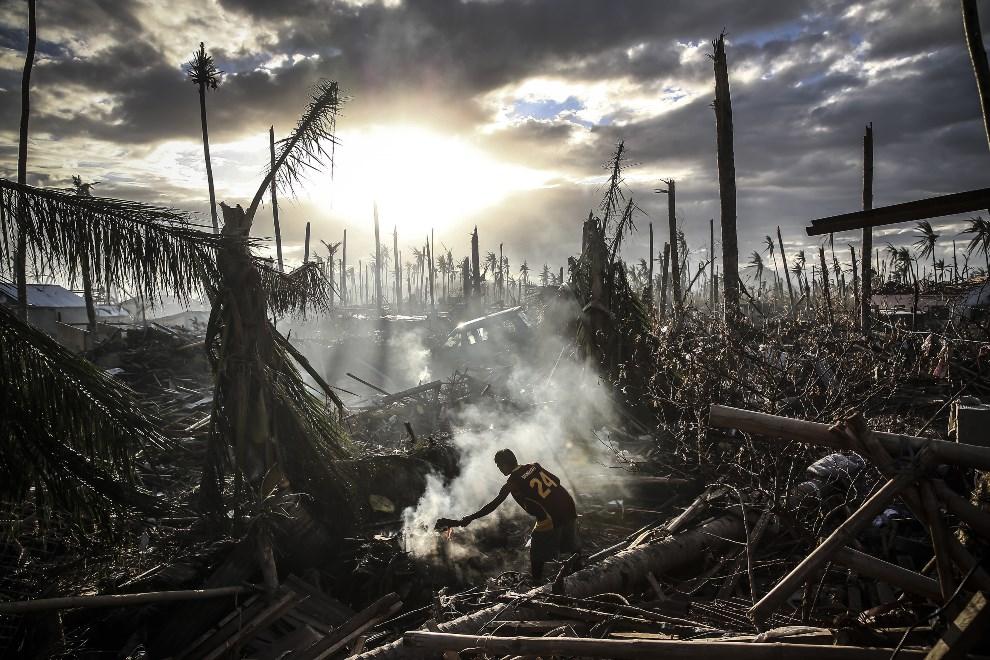 9.FILIPINY, Leyte, 19 listopada 2013: Mężczyzna rozpalający ogień pośród rumowiska. (Foto: Dan Kitwood/Getty Images)