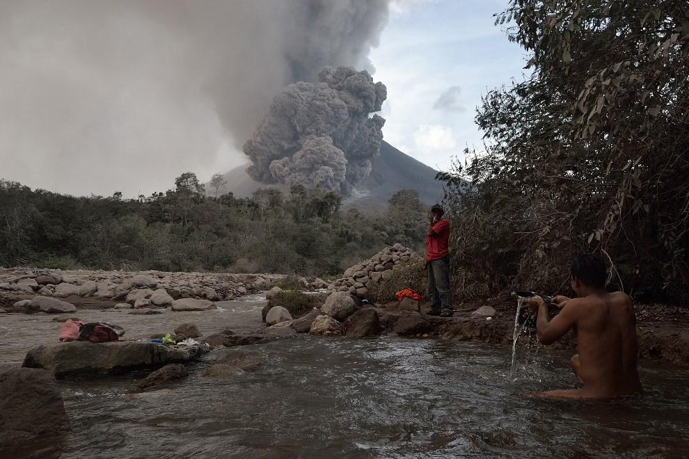 11.INDONEZJA, Karo, 21 stycznia 2014: Mieszkaniec pobliskiej wioski kąpie się w rzece (w tle erupcja wulkanu  Sinabung). AFP PHOTO / SUTANTA ADITYA
